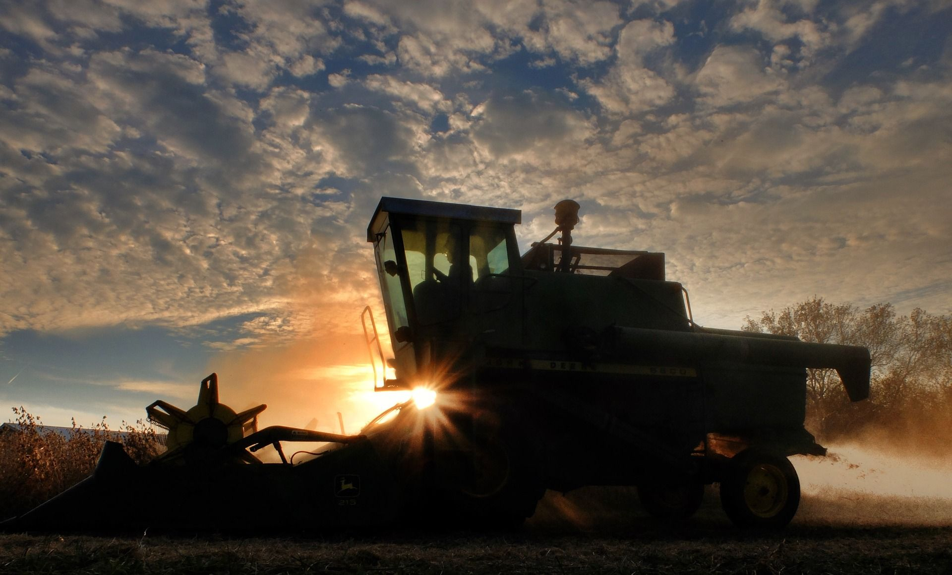 Combine harvester in front of a sunset
